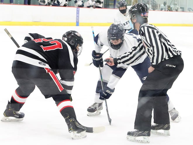 Exeter's Keegan Knight squares off with Bedford's Quinlan Kerr on a faceoff during Wednesday's Division I boys hockey game at The Rinks in Exeter.