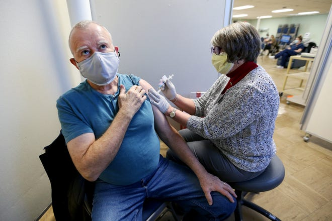 From left, Christopher Records receives his first dose of the Moderna vaccine from volunteer nurse Sandy Petrovich on Thursday afternoon at St. Christopher's Church in York.