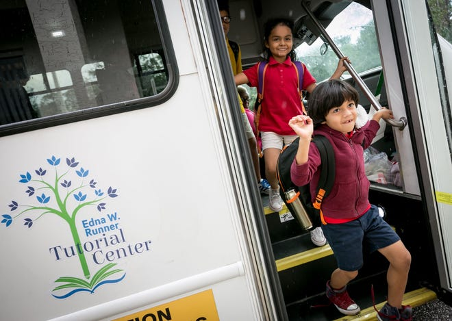 Kids arrive by bus after their school day to the Edna Runner Tutorial Center in Jupiter in November 2018.