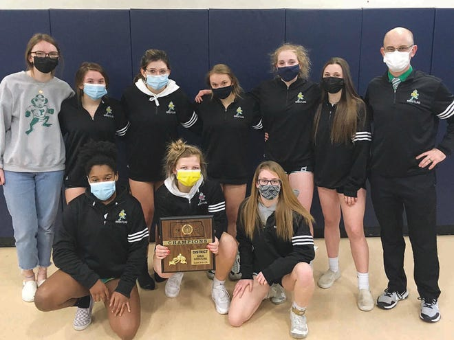 Members of the Pratt High School girls wrestling team pose with their first place District trophy on Saturday after a successful day of competition in Pratt. All seven members of the team qualified for Regional competition which will be next weekend.