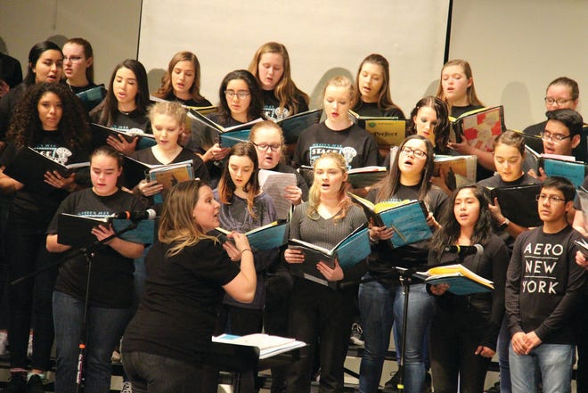 """Jenn Nelson directs the Perry High School Choirs in a medley from """"Beauty and the Beast"""" at the beginning of the 2019 Jukebox Variety Show."""