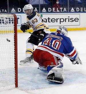 The Bruins' Brad Marchand scores the winning goal against Rangers goalie Alexandar Georgiev during overtime Wednesday night in New York.
