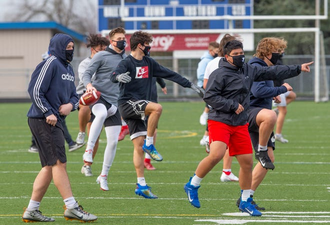 Churchill High School football players work out on the field Wednesday, the same day Oregon Gov. Kate Brown announced new guidance for outdoor contact sports, opening the door for the return of tackle football.