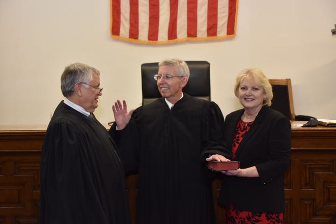 Sean Smith (center) gets sworn in as judge by retiring Judge John S. Campbell. Smith is joined by his wife, Janet.