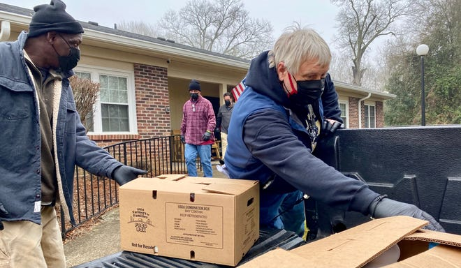 Lions Senior Village resident Ann Marie Udas, right, works with shelter volunteer Richard Lockett to distribute boxes of food Thursday morning.
