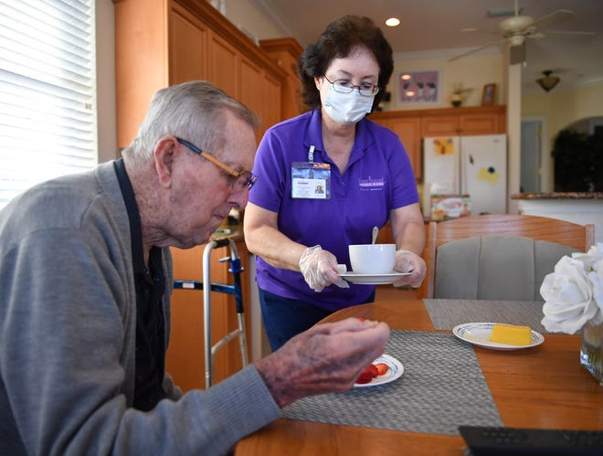 Ann Beres, a caregiver with Home Instead Senior Care, prepares a snack of fresh strawberries and a cup of tea for  her client, Forest Van Deventer, at his home in Venice, Florida.