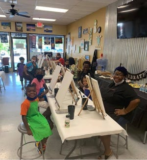 Sharon Jefferson, a Manatee County teacher, created a program to help children better navigate and understand virtual learning. Pictured here, some of the participants in Jefferson's mentoring and tutoring program attended an educational outing to a painting class with their peers.