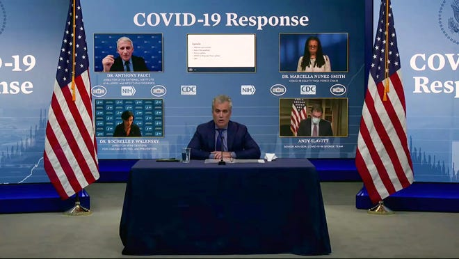 """In this Jan. 27, 2021, image from video, Jeff Zients, White House coronavirus response coordinator, speaks as Dr. Anthony Fauci, director of the National Institute of Allergy and Infectious Diseases and chief medical adviser to the president., Dr. Marcella Nunez-Smith, chair of the COVID-19 health equity task force, Dr. Rochelle Walensky, director of the Centers for Disease Control and Prevention, and Andy Slavitt, senior adviser to the White House COVID-19 Response Team,, appear on screen during a White House briefing on the Biden administration's response to the COVID-19 pandemic in Washington. President Joe Biden's team is styling itself on war footing as it attacks the coronavirus pandemic. Top aides say the administration is using every """"tool the federal government has to battle on every front."""" (White House via AP)"""