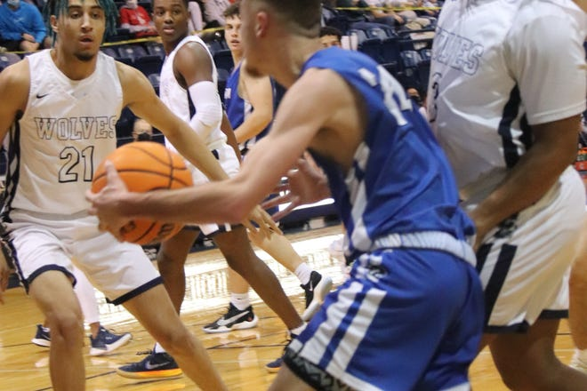 Shawnee's Kayden Shaw (left) and Jaylon Orange (right) defend a Harrah player during a recent home game.