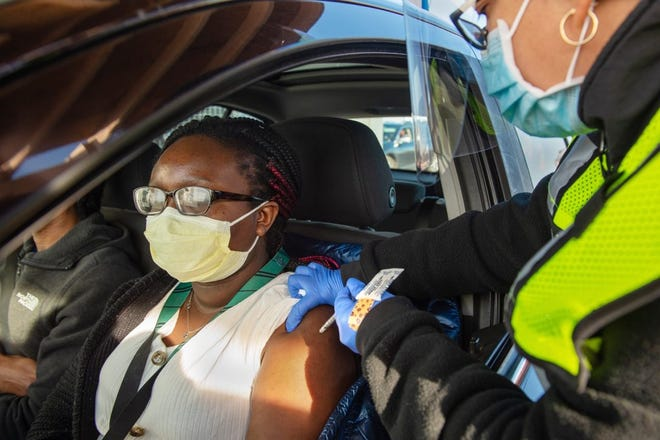 """Madeline Fall, 25, of Vernon, receives the first dose of the Pfizer vaccine from Lizmary Reyes, LPN, at Connecticut's largest drive-through vaccination clinic administered by Community Health Center, Inc. """"I'm the first one in my family to get this so I kind of feel like the guinea pig,"""" said Fall, a health care worker."""