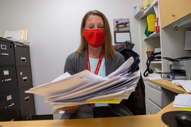 Denise Berkley, bookkeeper at the Lawrence Public Library, shows the stack of papers she has kept from fraudulent unemployment claims. Over half of the employees at the library have had bogus claims filed in their name, she said.
