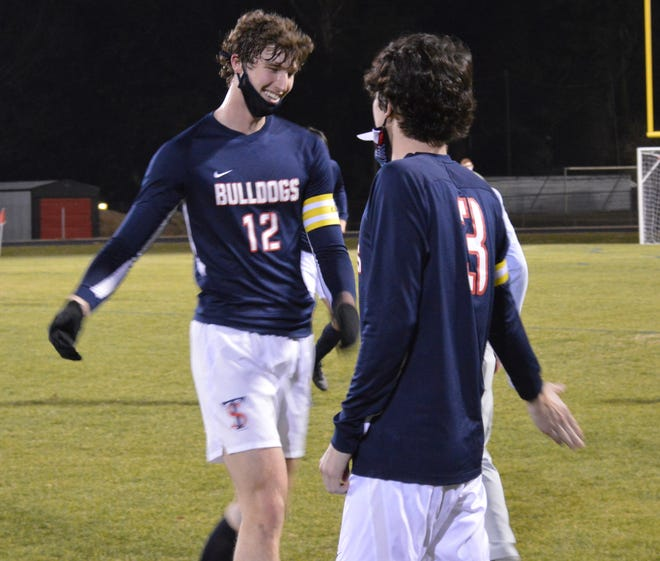 Davis Molnar (12), who is playing soccer and basketball in overlapping seasons for the Bulldogs, celebrates with senior captain Graham MacLeod after a 4-0 win against Gray's Creek.