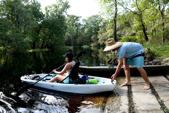 Kevin Krumwiede pushes his girlfriend, Liz Diaz, off the shore in their kayak from the boat ramp area at Rum Island Spring and Park, at a reopening of the park north of High Springs in September. After months of renovations Rum Island Spring and Park have reopened with a few new additions, new bathrooms, repaired boat dock and a cleaned-out and shored-up spring area.