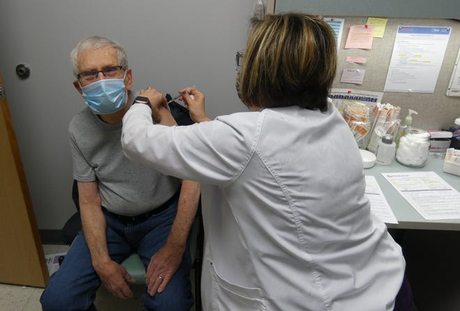 Erin Barnett, a public health nurse at Crawford County Public Health, administers a second dose of the COVID-19 vaccine to James Ash of Bucyrus.