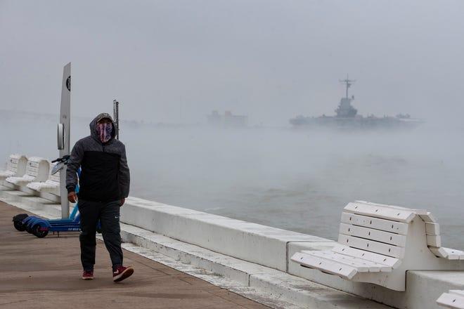 A man walks down Shoreline Blvd, Wednesday, Feb. 10, 2021. Corpus Christi prepares for a winter storm watch this weekend.
