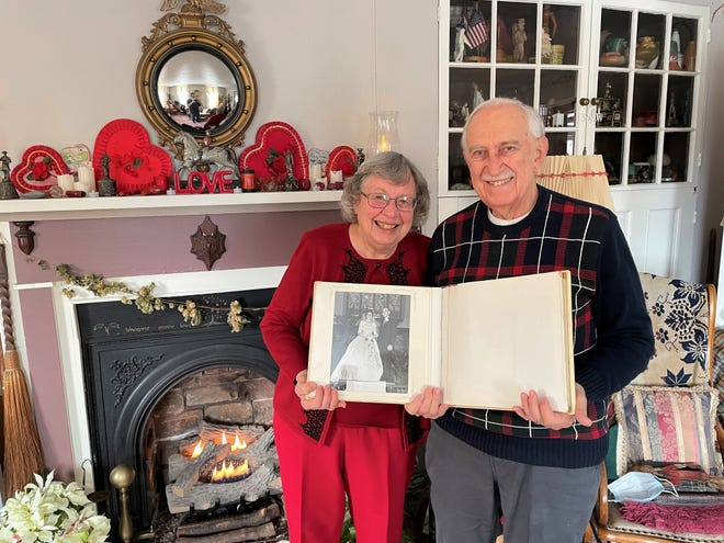 Alice and Dick Hoover of Coshocton have been married 57 years and originally met in a registration line at Otterbein University. They credit their long relationship to communication, faith in God and shared interests like history, music and the arts. They hold a photo album with a picture of them on their wedding day while standing next to the mantel in their home, decorated for Valentine's Day.