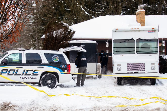 "Portage police investigate a missing persons case in Portage, Mich. Tuesday, Feb. 9, 2021. Police checking on a Kalamazoo-area man who didn't report to work online put yellow tape around the property. Officers also brought shovels to the backyard. Gary and Laura Johnson, both in their mid-60s, were not at their Portage home, but officers found ""signs of violence."" Public Safety Director Nick Armold says there's no ""rational explanation"" for their disappearance."