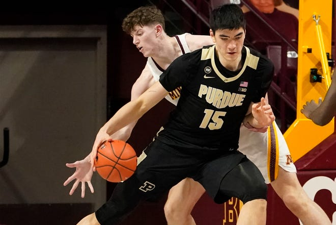 Minnesota's Liam Robbins, left, reaches for the ball as Purdue's Zach Edey (15) drives in the first half of an NCAA college basketball game, Thursday, Feb. 11, 2021, in Minneapolis.