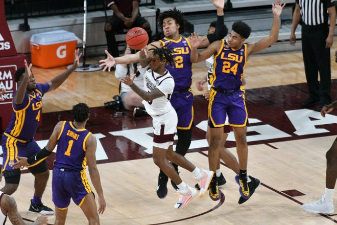 Feb 10, 2021; Starkville, Mississippi, USA; Mississippi State Bulldogs guard Deivon Smith (5) loses the ball while defended by LSU Tigers forward Trendon Watford (2) and guard Cameron Thomas (24) during the second half at Humphrey Coliseum. Mandatory Credit: Matt Bush-USA TODAY Sports