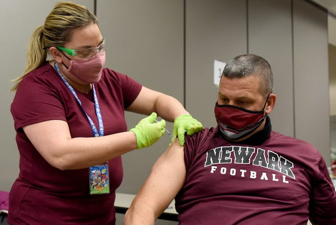 Licking County Health Department nurse Jessica Peterson administers the first dose of Pfizer's COVID-19 vaccine to Newark High School head football coach and health teacher Bill Franks during a vaccination clinic for faculty and staff from the Newark and Health school districts on Wednesday, Feb. 10, 2021.