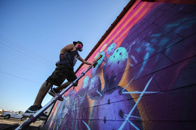 Muralist Sebastian Vela paints a mural depicting the Organ Mountains on the Ace Granite building at Harrelson Street and Union Avenue in Las Cruces on Thursday, Feb. 11, 2021.