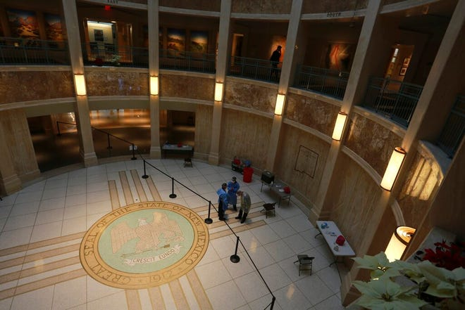 A man walks on the second floor of the New Mexico State Capitol building while emergency medical technicians wait to administer COVID-19 tests on Monday, Feb. 8, 2021, in Santa Fe, New Mexico. The building was closed to the public at the start of the pandemic. State leaders are holding most meetings virtually, with routine testing offered to legislators, staff members and the media.