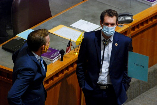 New Mexico state Sen. Gregg Schmedes, R-Tijeras, right, arrives at the opening day of a 60-day legislative session on Tuesday, Jan. 19, 2021, in Santa Fe, N.M. Fences, roadblocks, police and troops encircled the building as a precaution against federal warnings about the potential for violence. Plexiglass partitions have been installed on the floor of the House and Senate to protect legislators from coronavirus infection, and the Capitol is closed to the public to blunt the contagion.