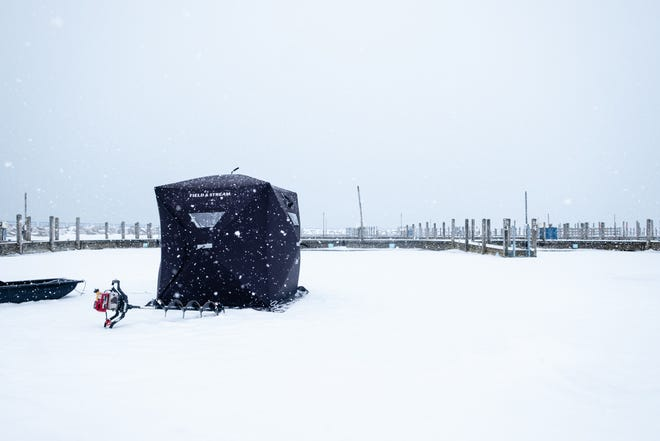 A heavy snow falls around an ice fishing shanty anchored on the ice in the marina in Lexington Thursday, Feb. 11, 2021.