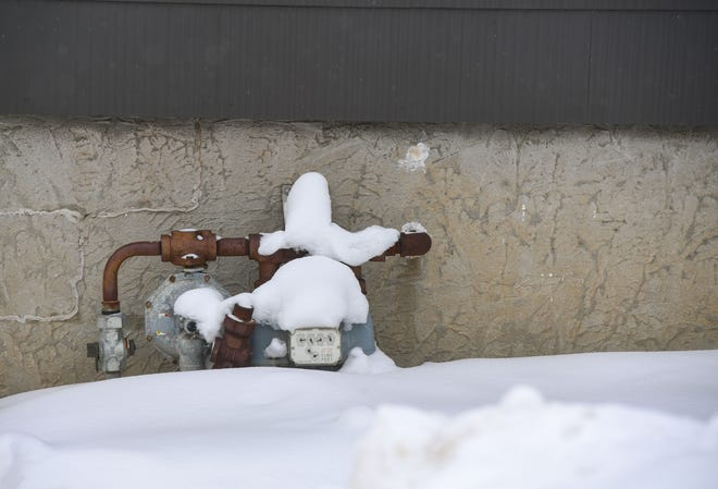 A utility meter is buried in the snow on the outside of a house on Thursday, Feb. 11, in Sioux Falls.