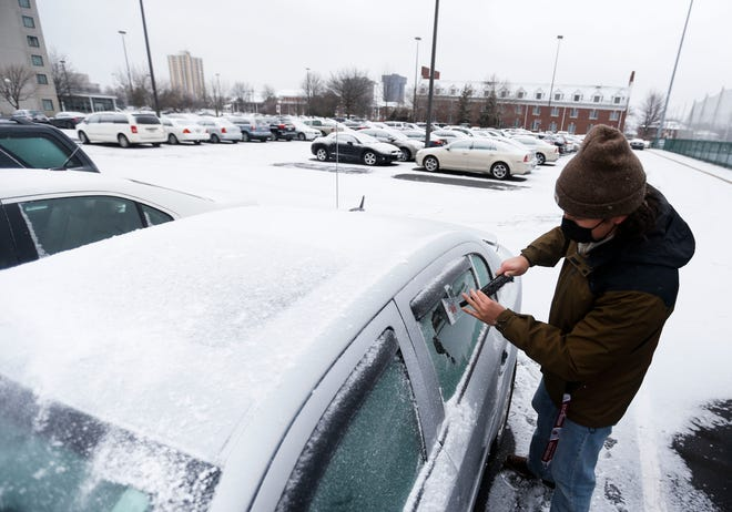 Missouri State student Grant Weaver scraps ice from the windows of his car in a parking lot on Thursday, Feb. 11, 2021.