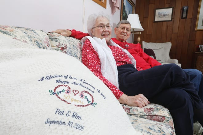 Jim and Pat Taylor talk about 65 years of marriage while seated in their New Concord home. At left is a blanket honoring their 50th wedding anniversary.
