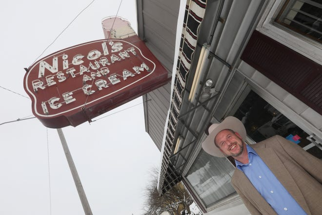 Lance Miller, an auctioneer with Ed and Ben Schafer Auctioneers, stands under the iconic Nichol's Restaurant sign in Zanesville. The sign is up for auction and has generated interested from around the world.