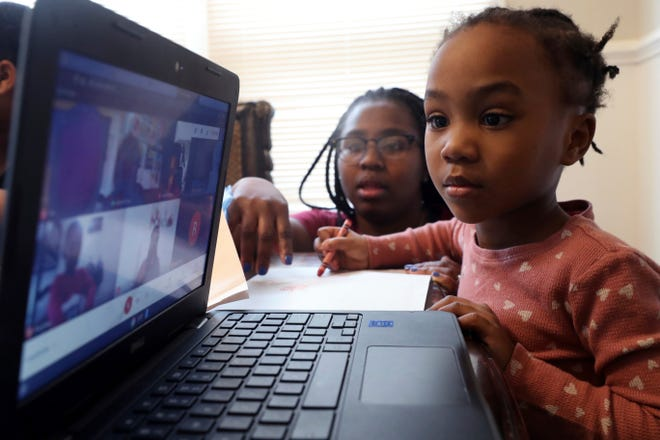 Lear Preston, 4, attends her Scott Joplin Elementary School virtual classes as her mother, Brittany Preston, background, assists at their residence in Chicago's South Side, Wednesday, Feb. 10, 2021.