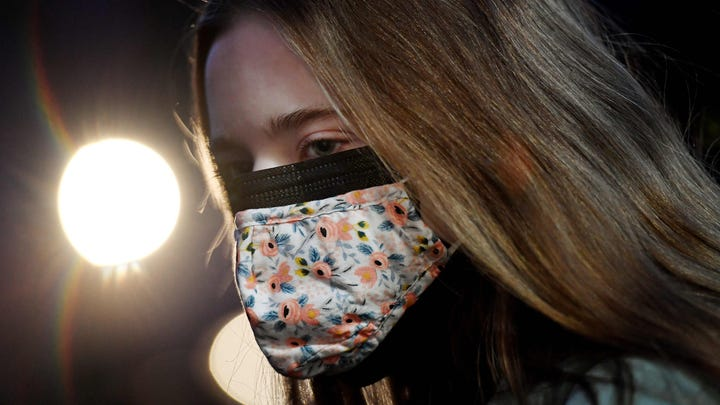 This illustration shows a woman wearing two facemasks, a cloth mask over a surgical mask, in Arlington, Va, on Feb. 8, 2021.