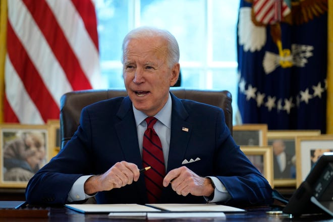 President Joe Biden signs a series of executive orders on health care, in the Oval Office of the White House, Thursday, Jan. 28, 2021, in Washington. The Democratic push to raise the minimum wage to $15 an hour has emerged as an early flashpoint in the push for a $1.9 trillion COVID relief package.