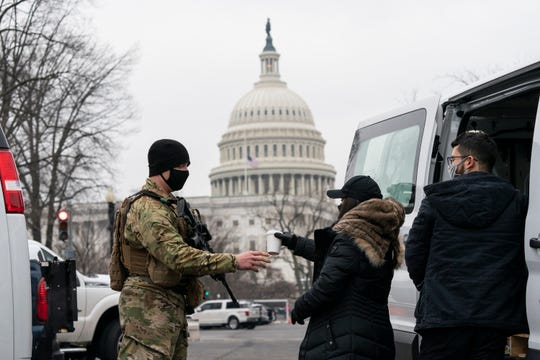 A U.S. Army National Guard soldier gets a cup of coffee as he guards the perimeter of the U.S. Capitol on Feb. 11 in Washington.
