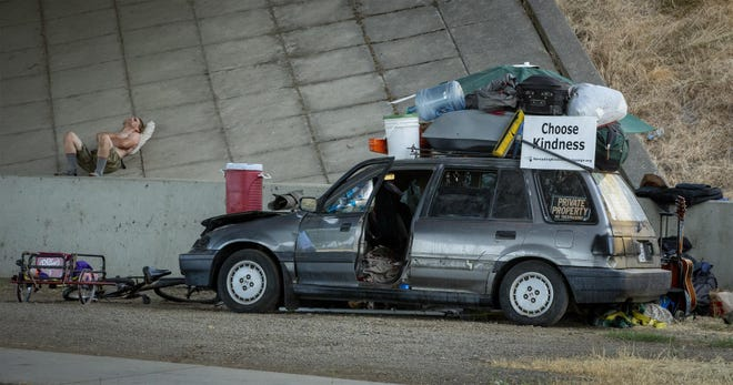 A man rests near a vehicle parked under Interstate 5 at Gateway Street in Springfield, Or. To have a wider scope of homelessness in the area, local government and its nonprofit partners are using the Homeless By-Name List, which tracks people who are receiving services and who are unhoused from a number of local agencies monthly.