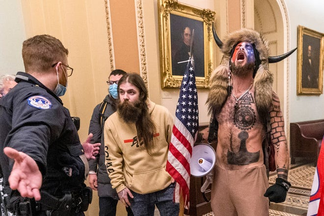 Supporters of President Donald Trump, including Jacob Chansley, right with fur hat, are confronted by U.S. Capitol Police officers outside the Senate Chamber inside the Capitol in Washington on Jan. 6, 2021.
