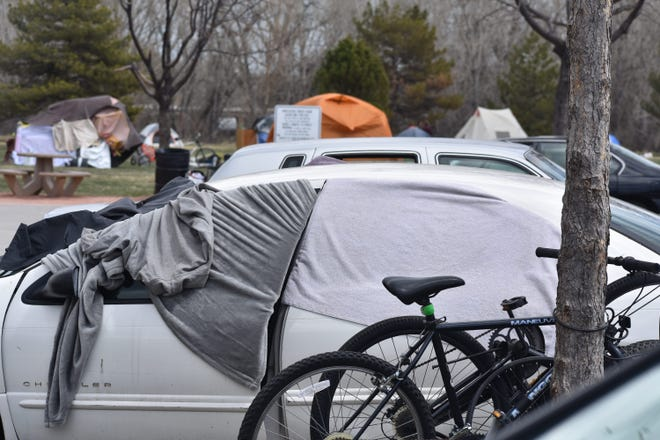 A vehicle serves as shelter April 8, 2020, in the parking lot of the Northside Aztlan Community Center in Fort. Collins, Co., where in recent days a homeless tent city has sprung up. The center is providing aid to those facing homelessness during the coronavirus pandemic.