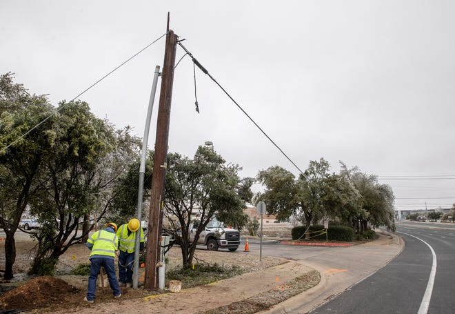 Pike Electric workers prepare to replace a utility pole Friday that snapped along North Lake Creek Parkway near Lakeline Mall Drive.