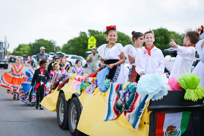 Members of the Highland Park Elementary Ballet Folklorico ride and walk down the street during the 2018 Deutschen Pfest Parade in Pflugerville.