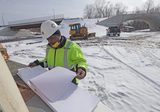 Darcius Linton, a construction manager and inspector from G. Stephens Inc., looks over plans Thursday the Evans Avenue Project in Akron.