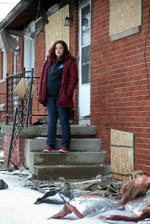 Emily Tompkins of Barberton stands on the front step of her apartment that was destroyed by a fire Feb. 8 while she was at work.