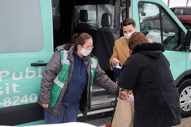 Ashland Public Transit driver Crystal Baker and Mayor Matt Miller greet and hand Natalia Caley Valentine's Day goodies as she boards the transit vehicle on her way to work on Friday, Feb. 12, 2021. TOM E. PUSKAR/TIMES-GAZETTE.COM