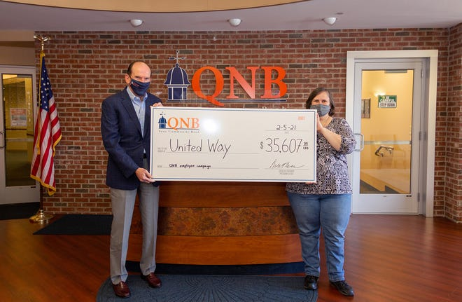 Dave Freeman, left, president and CEO of QNB Bank, and Patti Cole, executive assistant of QNB Bank, present an oversized check to commemorate the $35,607 donation to United Way.