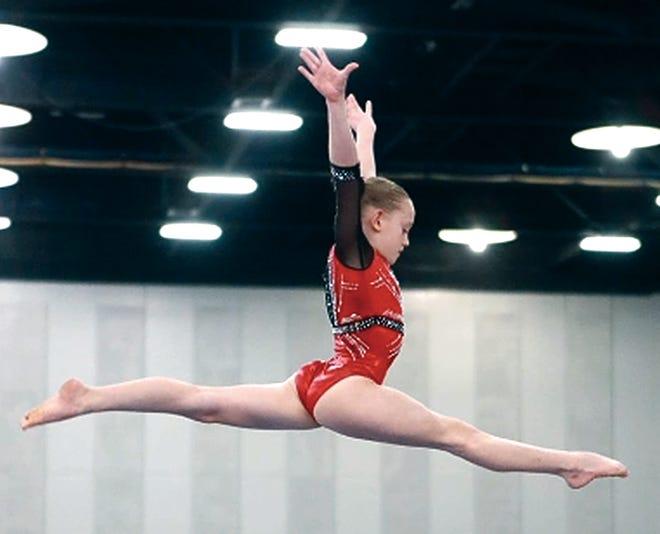 Bartlesville Gymnastic Club's Annika Dennis soars high in the air during a balance beam routine.