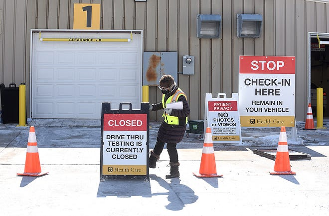 Julie Clark, a nurse at University Hospital, places signs at the Mizzou North drive-thru COVID-19 testing station Friday. The site will be closed this weekend due to cold weather and is scheduled to reopen at 8 a.m. Tuesday.