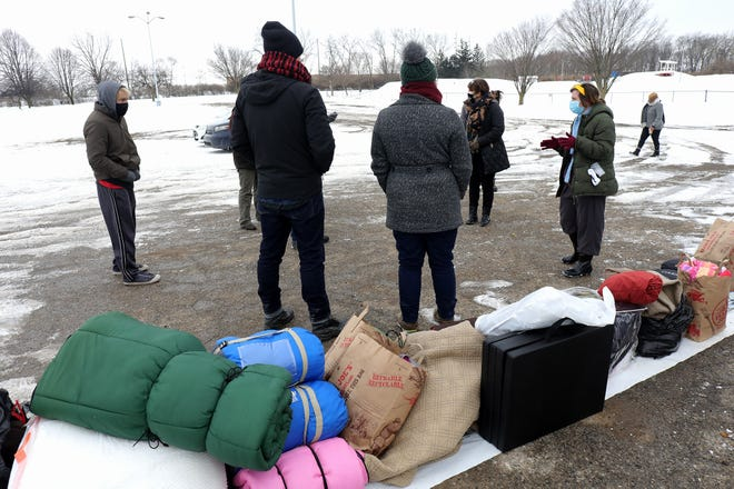 Local homeless advocates stand in the parking lot of Heer Park on Friday, where they gathered to give needed supplies to the homeless. The advocates meet people in the homeless community at the park on West Williams Road off South High Street on Friday and Saturday evenings to distribute tents, clothing, sleeping bags and even Narcan.