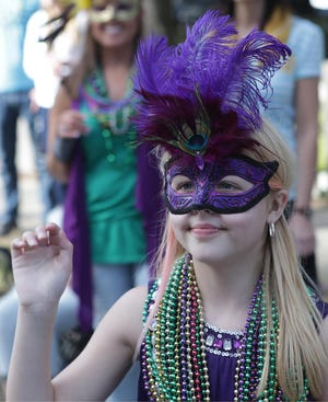 Young lady wearing a Mardi Gras mask in this 2016 file photo.