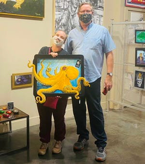 Artist Michael Slage (right) poses with a piece just sold to Shannon Eaton (left) at the 7887 Collective in Houma.